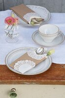 Coffee cup and cake plates on white runner on wooden table