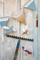 Hand-made bunting with lace trim and paper birds hung on wooden wall