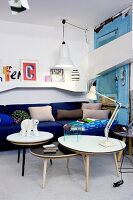 Set of coffee tables in front of royal-blue couch and white wall-mounted shelves in eclectic interior