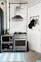 Stainless steel gas cooker below extractor hood against white-tiled wall and blue and white stripes rugs on rustic wooden floor