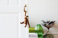 Monkey figurine hanging from handle of sliding door, green glass vase and magazine rack in living area