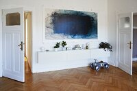 Blue painting above low sideboard against white wall in living room with herringbone parquet floor