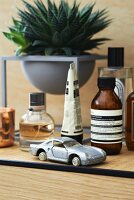 Various small bottles, succulents and model car on bathroom cabinet