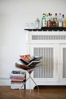 Bottles of various spirits on top of vintage-style radiator cover behind magazine rack