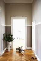 Grey-painted walls, white door frame and herringbone parquet floor in hallway