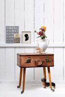 Jug of flowers on top of DIY table made from vintage suitcase