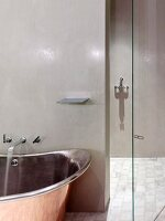 Retro, industrial-style designer bathtub and walk-in shower with polished, glazed walls