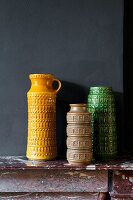 Collection of retro vases of various colours on mantelpiece against black wall