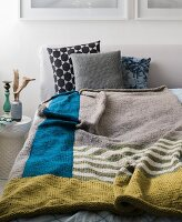 Homemade knitted colour block blanket made from a mixed wool yarn