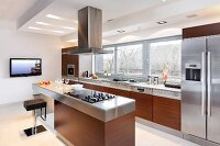 Luxury kitchen with exotic-wood fronts and stainless steel fitted appliances, island counter and plasma TV