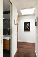 Hallway with skylight, pictures on wall and open door with view of washstand to one side