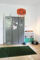 Basketball basket mounted on locker and strip of artificial grass on wooden floor