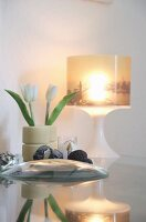 Cityscape picture on illuminated lampshade and plastic tulips arranged in old skateboard wheels