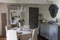 Chairs with pale loose covers around set dining table next to sideboard in rustic dining room