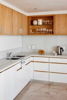 L-shaped kitchen counter with white worksurface and base units below solid wood wall units with one open-fronted unit
