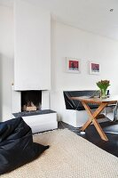 Wooden table and masonry bench next to open fireplace with black beanbag in foreground