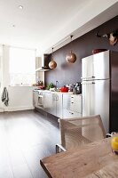Stainless steel kitchen counter and fridge-freezer and Oriental-style pendant lamps against dark wall