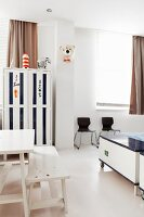 White-painted table and bench next to trunk on castors in teenager's bedrom