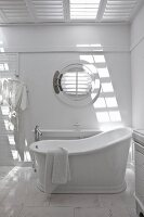White bathroom with porthole window and vintage-style free-standing bathtub