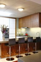 Open-plan, modern kitchen with breakfast bar and elegant, brown leather bar stools; designer ambiance