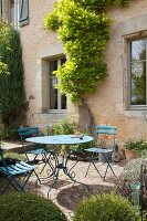 Blue table and folding chairs on terrace outside French manor house