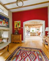 Ethnic rug, red wall and open doorway with view into open-plan interior