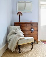Antique easy chair and chest of drawers in corner of room painted pale blue