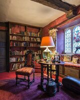 Antique chair and table lamp on table in front of window seat in traditional library