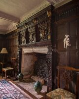 Elegant, antique fireplace with carved wooden surround on wood-panelled wall