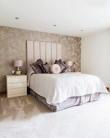 Double bed with tall upholstered headboard against patterned wallpaper in elegant bedroom
