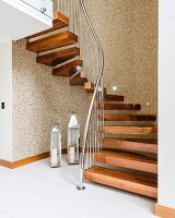 Winding staircase with wooden treads and stainless steel balustrade above lanterns on tiled floor