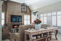 Lounge area, carved wooden console table against back of sofa and flatscreen TV on wall painted light brown