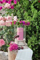 Pink candle in lantern and wreath of pink Sweet Williams in garden