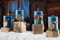 Four lit blue Advent candles on wooden blocks amongst snow