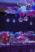 Table festively decorated with flower arrangements for an Indian wedding below glass baubles hanging from suspended branches