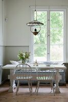 Pale grey chairs and vintage table in dining area below lattice window
