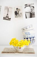 Yellow primula in vintage bowl in front of postcards and stacked bowls
