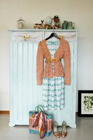 Vintage wardrobe painted pale blue decorated with vintage china ornaments and woman's clothing