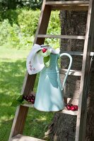 Old water pitcher and cherries on wooden ladder leaning against tree