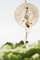 Dreamcatcher made from crocheted doily, feathers and sequins