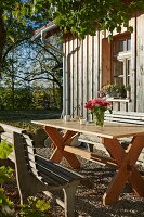 Rustic seating area in autumn sunshine outside wooden house