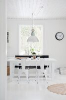 Industrial-style lamp and chairs in white dining room