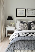 Table lamp on bedside table next to double bed with white, wooden lattice headboard and black and white scatter cushions