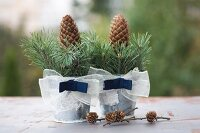 Two zinc buckets decorated with ribbons, spruce twigs and pine cones next to larch cones on surface