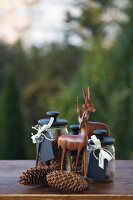 Autumn arrangement of storage jars with black lids and labels, wooden antelopes and pine cones