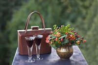 Autumn still-life arrangement with posy of berries in brass vase, vintage handbag and two aperitifs