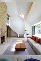 Exotic-wood coffee table and pale grey corner sofa in open-plan, high-ceilinged interior with staircase in background