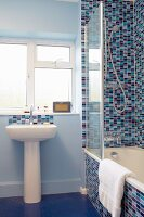 Pedestal sink below window next to bathtub against wall tiled in various shades of blue and red