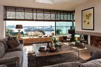 Rustic coffee table and sofa set in living room with view of a container ship sailing past on the Elbe through panoramic window