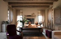 Interior of old renovated villa; rustic wooden table against back of sofa and draped, floor-length curtains on windows